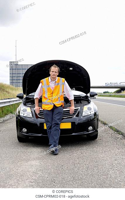 motorist, wearing a safety vest, sitting on the bumper of his broken car with open hood on the shoulder of a motorway, waiting for assistance to arrive