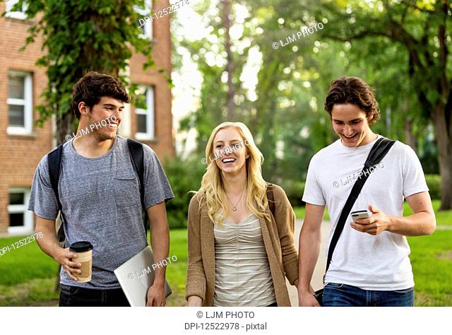 Three friends walking and talking on the university campus; Edmonton, Alberta, Canada