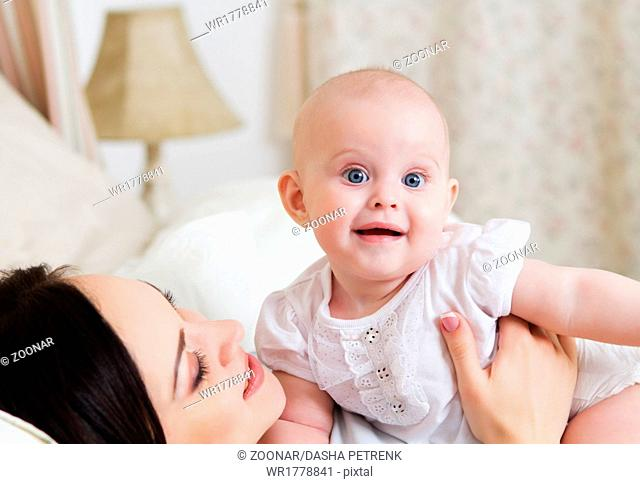 Happy smiling mother with six month old baby girl