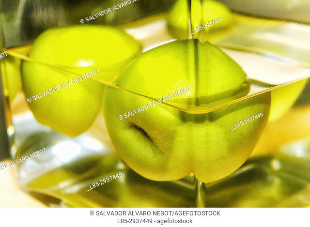Half-submerged apples in glass bowl