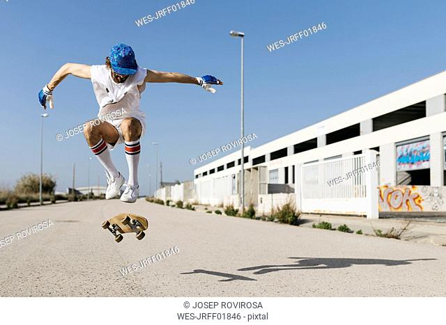 Sportive man jumping above ground with skateboard performing trick
