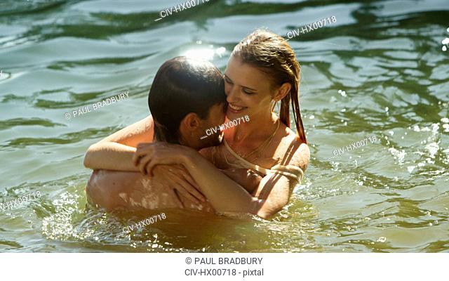 Affectionate couple hugging and swimming in sunny lake