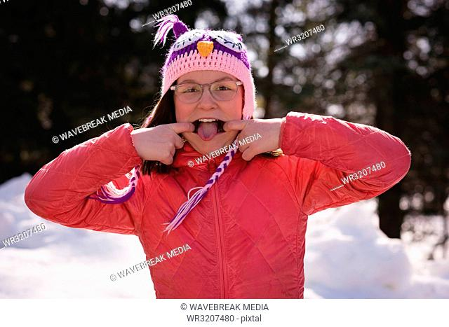 Girl pulling funny faces during winter
