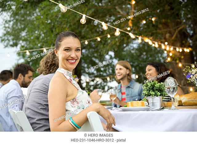 Smiling woman sitting with friends at outdoor dinner party