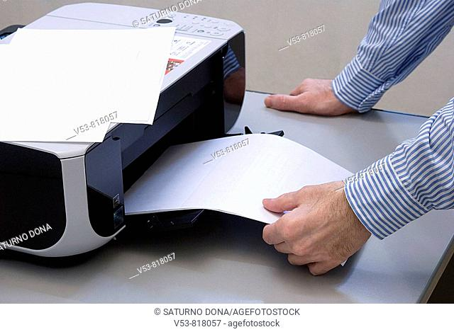 man in the office removing paper from printer