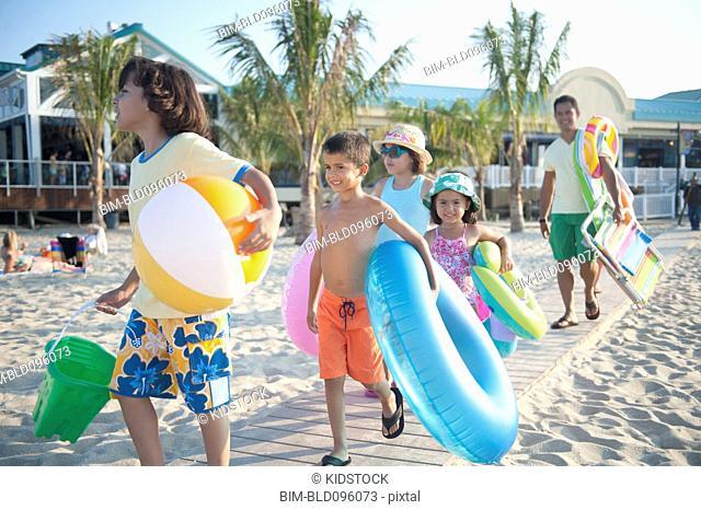Hispanic family walking to beach