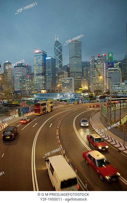Central Hong Kong traffic passes through construction zone at dusk, with skyline