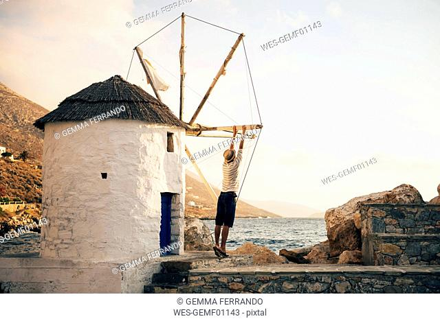 Greece, Amorgos, Aegialis, back view of man holding the blades of wind mill