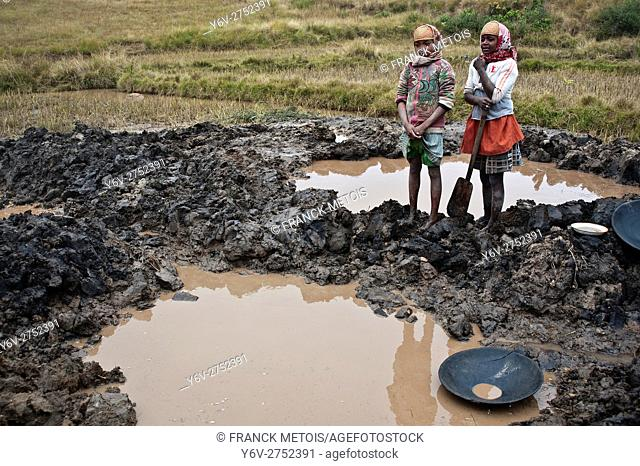 Two girls working as gold digger. In the foreground, a abandoned pit full of water. Depth of the pit is around 2 meters. The pit is full of water because...