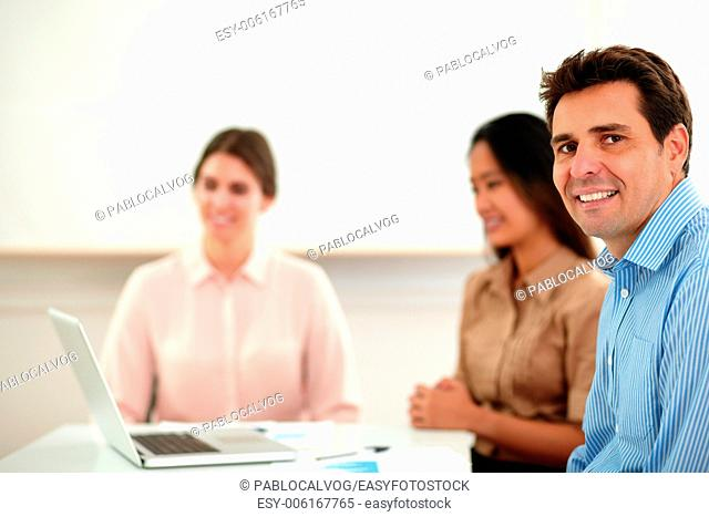 Portrait of handsome businessman looking and smiling at you while sitting with his colleagues during a meeting on office