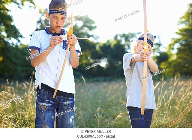 Two young boys holding bow and arrow
