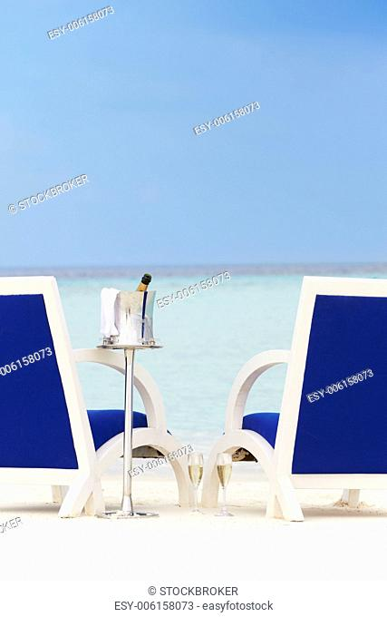 Bottle Of Champagne Between Chairs On Beautiful Beach