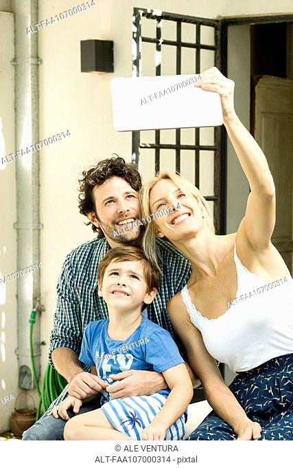 Family with one child posing for selfie taken with digital tablet
