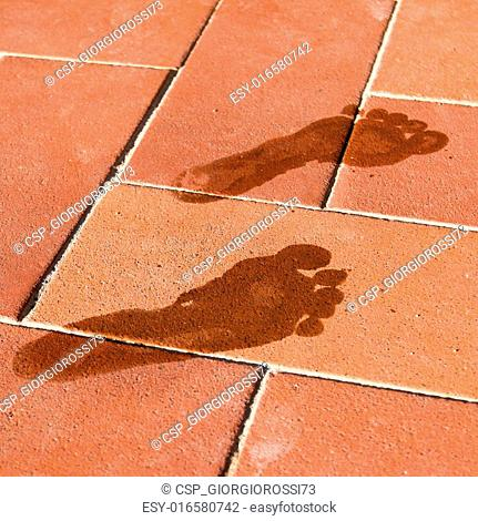 woman wet foot imprint on a red tile floor