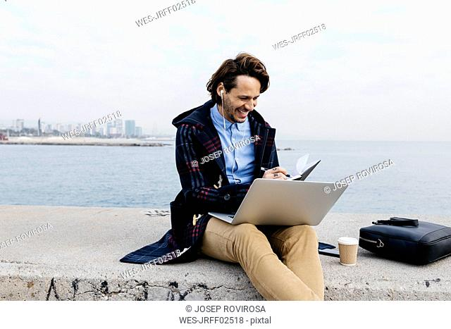 Spain, Barcelona, smiling man sitting at the sea working with laptop and notebook