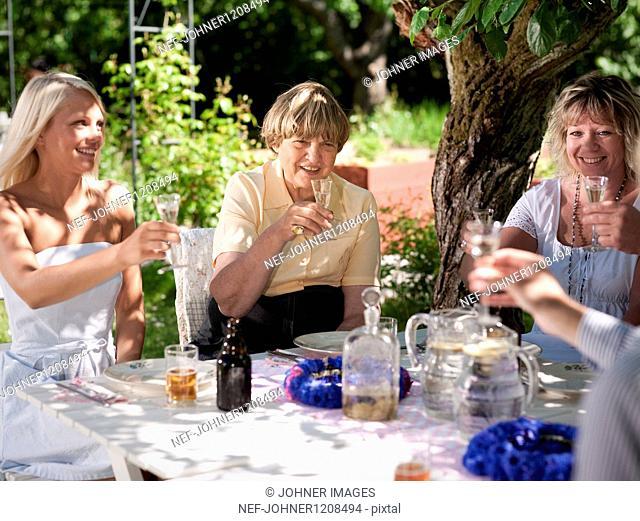 People having drinks in garden, smiling