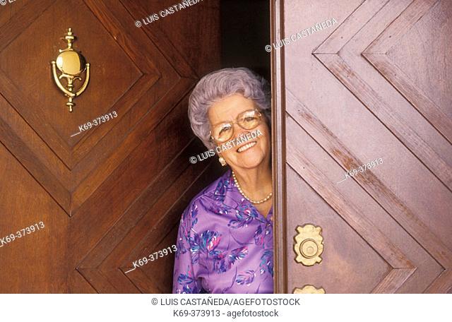 Old woman smiling at doorstep