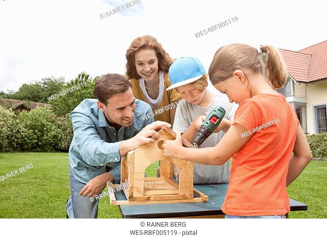 Family building up a birdhouse together
