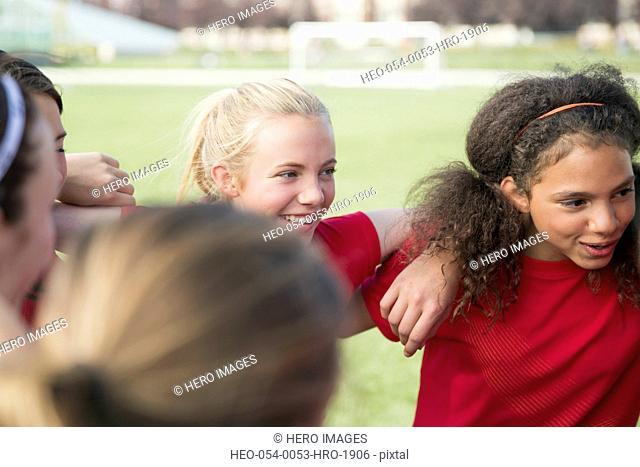 Teenage girls in soccer team huddle
