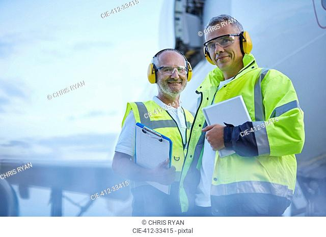 Portrait confident air traffic control ground crew workers with digital tablet near airplane on tarmac