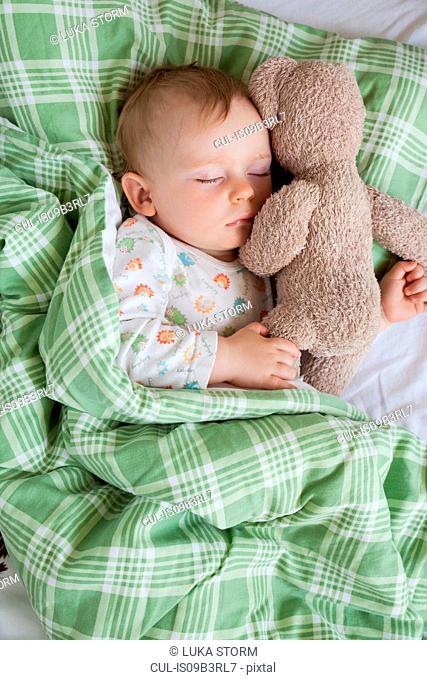 Overhead view of baby boy asleep on bed holding teddy bear
