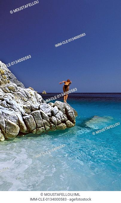 Woman jumping from a rock on Seychelles beach  Ikaria, Northeastern Aegean Island, Greece