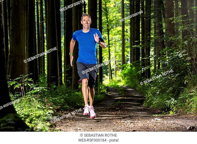 Smiling man jogging on forest track