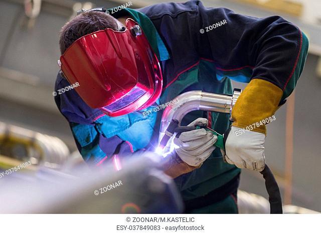 Industrial worker welding in metal factory
