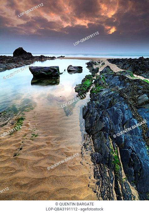 England, Cornwall, Sandy Mouth. Rock formations and pools of water on Sandy Mouth beach at dusk
