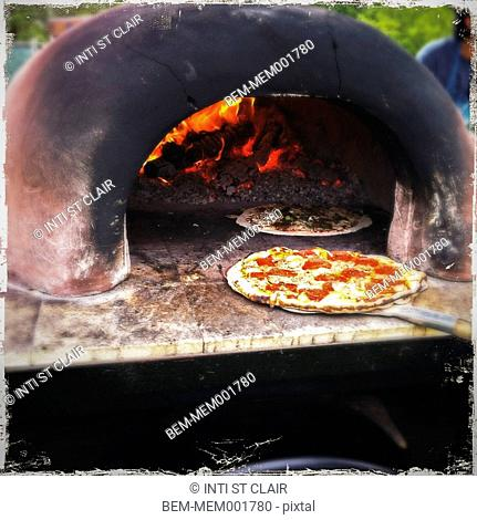 Pizzas cooking in outdoor wood oven