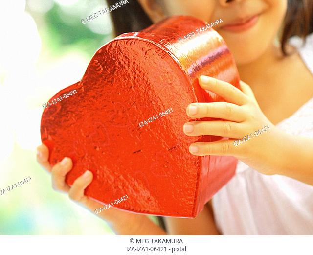 Close-up of a girl's hands holding a heart shape box