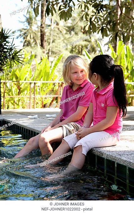 Thailand, children sitting on edge of swimming pool