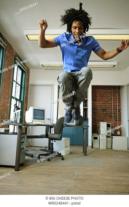 A young man leaping high in the air in a loft-style office