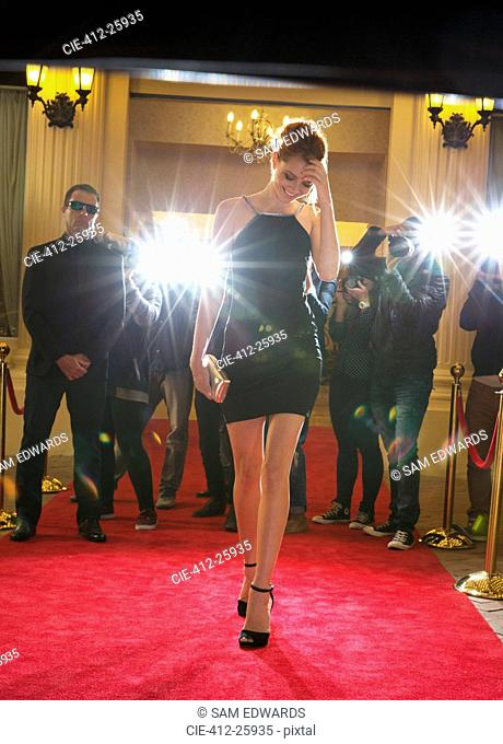 Celebrity in black dress being photographed by paparazzi photographers at red carpet event