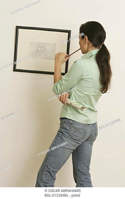 rear view of woman looking at picture on the wall