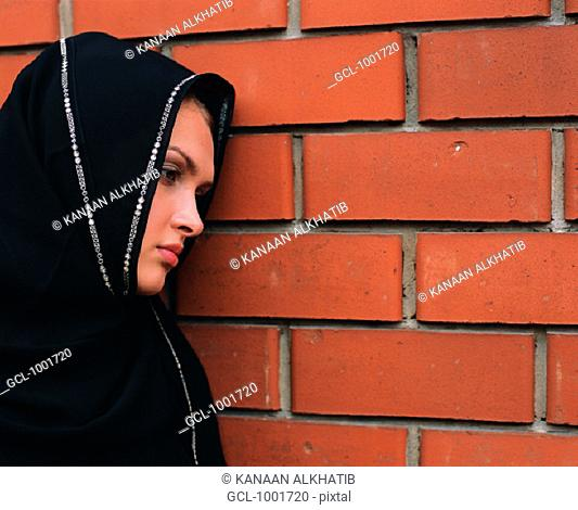 Pensive woman leaning against a wall