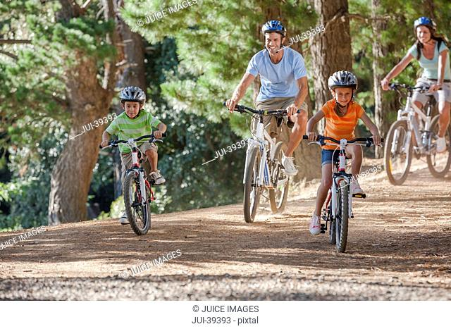 Happy family riding mountain bikes in woods
