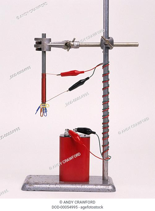 Electromagnetic experiment, battery connected to wires on clamp stand, lifting paper clips