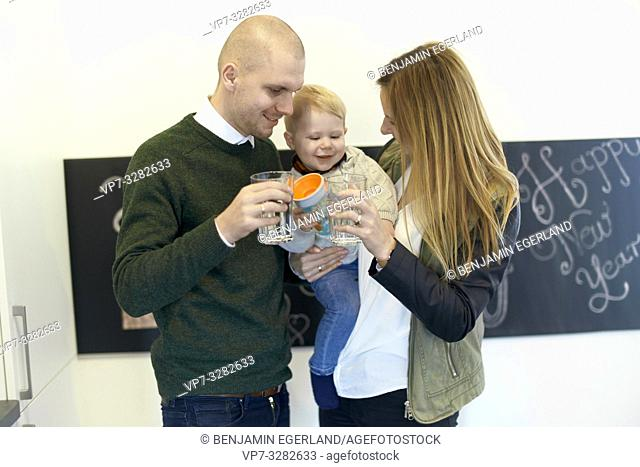 parents with baby toddler child in arm, water glasses in hands, family staying hydrated, drinking water, in Cottbus, Brandenburg, Germany