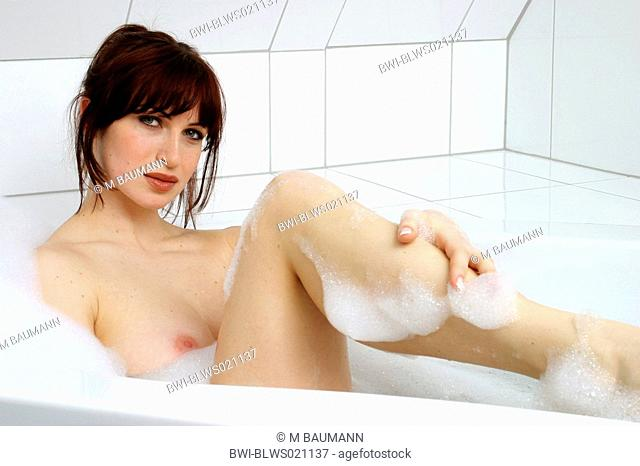 dark-haired woman taking foam bath