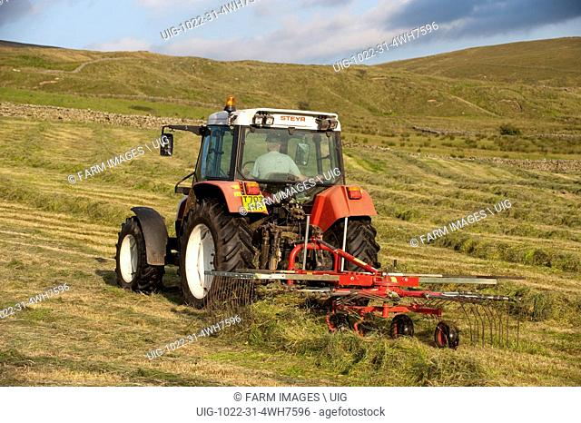 Rowing up grass on a hill farm to make big bale silage. (Photo by: Wayne Hutchinson/Farm Images/UIG)