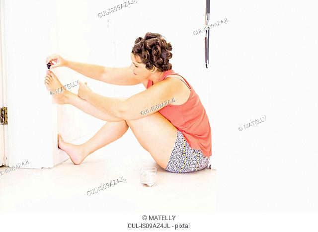 Woman with foam rollers in hair, painting toenails