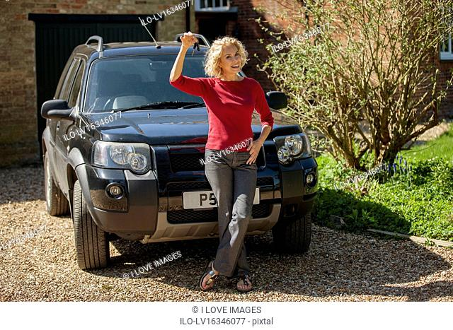 A mature woman holding the keys to her new car