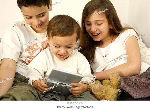 Brothers and sister playing to a video game Nintendo DS