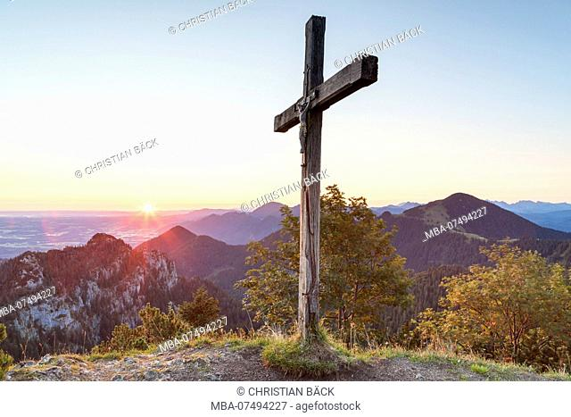 Sunrise at the summit cross of the Sulten behind it the Chiemgau Alps with the Gedererwand and Hochplatte, Chiemgau, Upper Bavaria, Bavaria, southern Germany