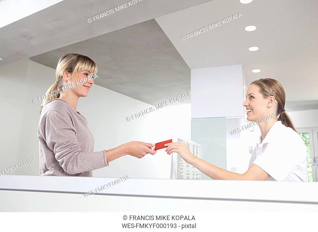 Germany, Patient giving insurance card to receptionist in dental office