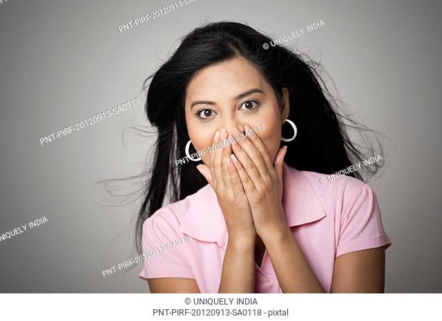 Woman with hands covering her mouth