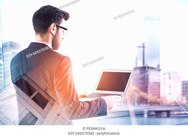 Attractive european businessman using laptop on abstract blurry city background. Communication and network concept. Double exposure