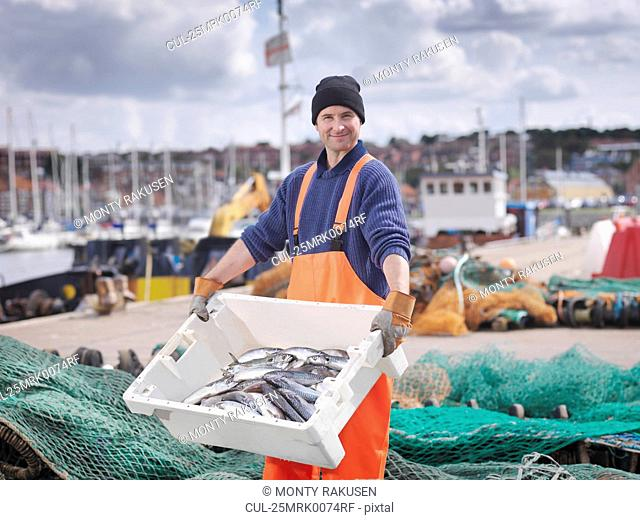 Fisherman with box of fish in harbour