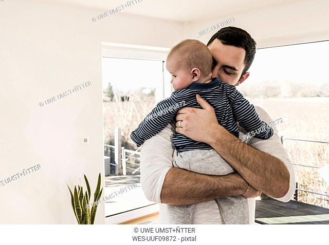 Father holding and hugging his baby son, standing in comfortable home